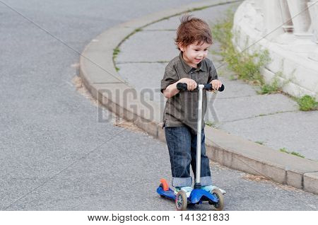 Cute little boy riding push scooter on the street
