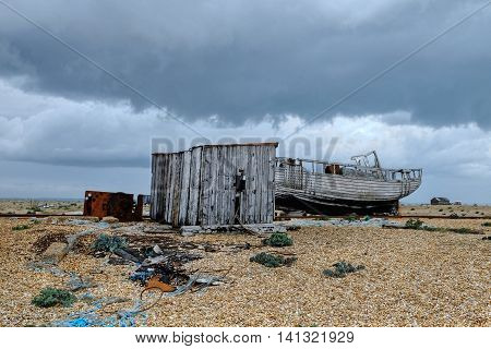 An overcast day on Dungeness, kent, with disused rail tracks, abandoned boat sheds and wrecks on the shingle beach.