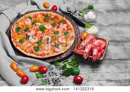 Pizza with shrimps grated cheese balls cherry tomatoes yellow red on gray linen towel with lace cutting board round served on light background white wooden surface
