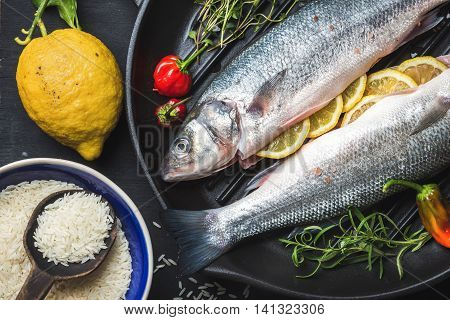 Raw uncooked seabass fish with rice, lemon, herbs and spices on black grilling iron pan over dark background, top view, horizontal composition