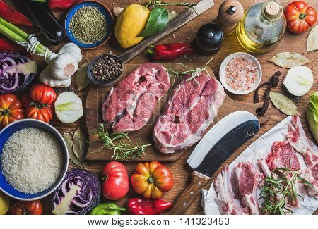 Ingredients for cooking meat dinner. Raw uncooked lamb meat assortment, rice, olive oil, spices and vegetables over wooden background, top view, horizontal composition