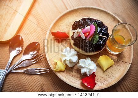 Blueberry cheesecake on wooden plate, Cake with coffee in coffee shop or in the restaurant, Blueberry cake with jam on wooden plate and set of cake which the cake is homemade cake.