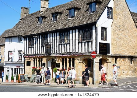 BURFORD, UNITED KINGDOM - JULY 20, 2016 - Tourists standing outside Burford House Tea Rooms along The Hill shopping street Burford Oxfordshire England UK Western Europe, July 20, 2016.