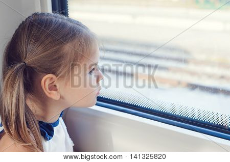 Little girl looking out the window of the train. She  looking through window, She travels on a train.