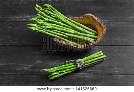Asparagus green on dark black background wooden surface asparagus beam tied with rope and twine in wooden bowl especially for asparagus handmade from olive wood