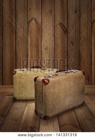 Two vintage suitcases on rough wooden plank background
