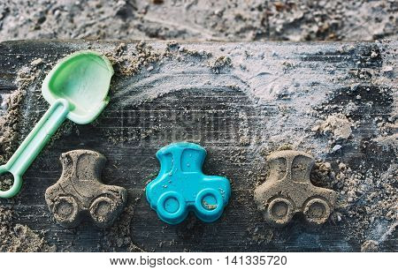 Concept of children toys on a child sandbox on the sand and wooden background with copy space