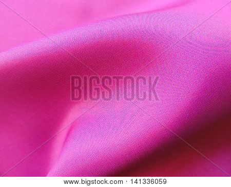 Pink, wavy textile or cloth, close-up. Pink textile background.