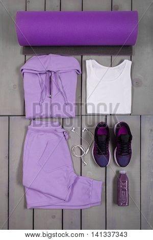 Overhead view woman's workout outfit. Female sports equipment. Purple sport pant shoes suit mat water bottle white headphones and shirt on grey wooden background. Top view.