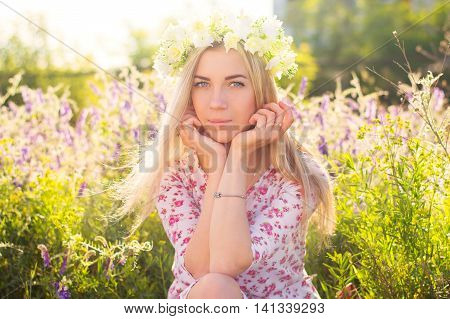 Young woman with long blond hair with flower coronet sitting in the field with purple flowers