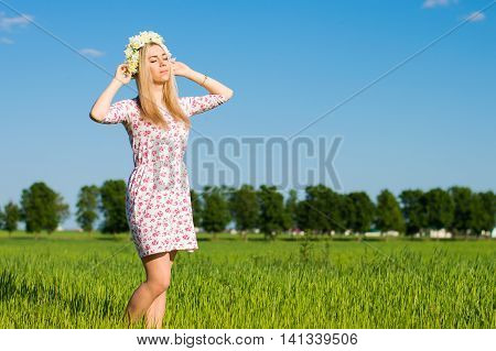 Young blond woman with long hair dressed in a dress with floral pattern standing in the green field blue sky on the background
