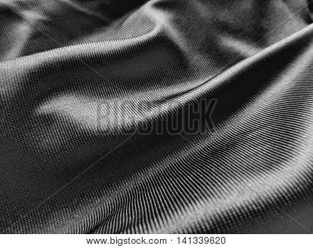 Black satin textile or cloth, closeup. Textile background.