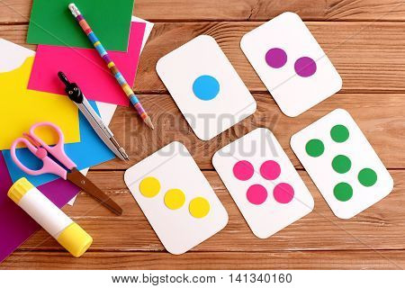 Education cards for kids. Learning colours. Teaching children to count. Scissors, pencil, glue, colored cardboard sheets on a wooden table. How to make flash cards for kids. Step