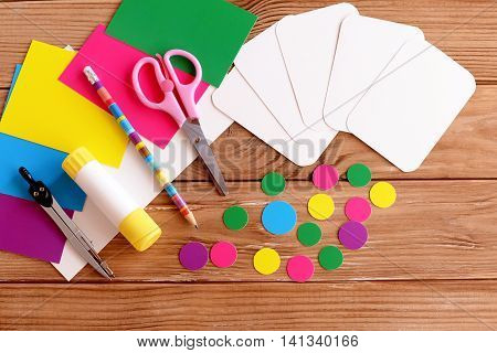 Cut cards and circles, scissors, pencil, glue, colored paper sheets on a wooden table. How to make educational flashcards from cardboard for teaching children. Top view. Tutorial. Step