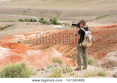 a photographer with a backpack photographed in the mars mountains