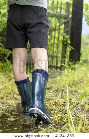 Child in shining gumboots goes on a footpath on the puddle close up on a rainy summer day