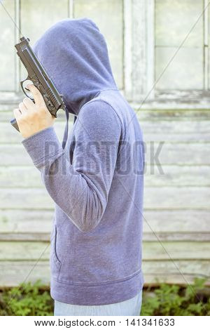 Man in hoodie holding in his hand pistol on a background the old wooden walls outdoors