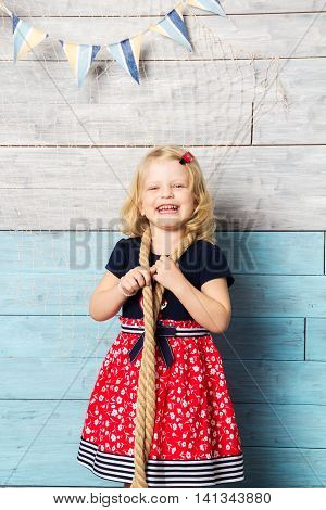 little girl with rope looking at camera and laughing closeup