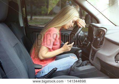 Young woman falling asleep in car