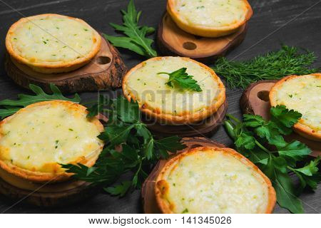 Little mini pizza tartlets with cheese and fresh herbs lettuce dill parsley. Mini pizza on dark black background wooden surface