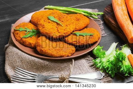 Orange carrot cutlets for vegetarian health food peeled carrots sliced carrots for cutlets into strips silver forks asparagus fresh herbs on dark black wooden background in rustic style