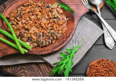 Buckwheat cereal with roasted mushrooms in wooden plate raw buckwheat to cereal asparagus silver fork and spoon green lettuce leaves on dark black background wooden surface