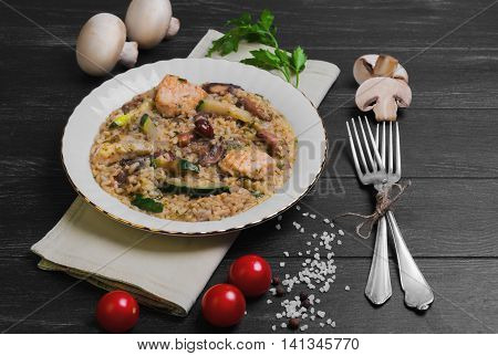 Rice cooked risotto with chicken meat and mushrooms and vegetables ingredients for risotto cherry tomatoes zucchini squash mushrooms champignons on white porcelain plate silver fork dark black wooden background