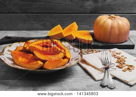 Baked pumpkin pieces on white vintage porcelain plate raw pumpkin pieces cut for baked napkin tissue pumpkin seeds on bright white background wooden for Halloween