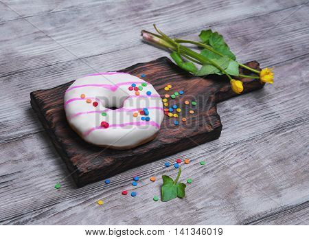 Donut with white and pink icing sprinkled sprinkling colored for donuts yellow flowers on light wooden background