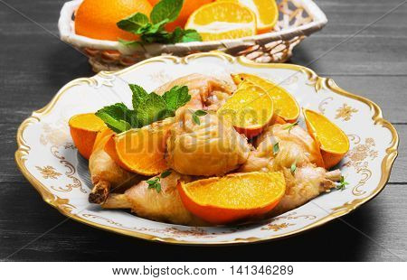 Baked chicken drumstick with baked oranges fresh oranges cut for chicken green mint thyme white porcelain plate cloth wicker basket on dark black wooden rustic background