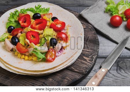 Delicious grilled chicken fresh vegetables homemade tortillas vegetables for stuffing tortillas rustic cutting board on gray wooden background