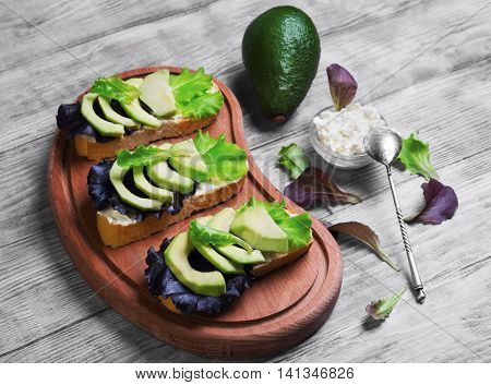 Three sandwiches with avocado cottage cheese ricotta lettuce ingredients for sandwiches cream cheese in bowl creeping fruit avocado on cutting board on light white wooden background