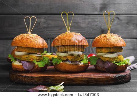 Vegan burgers with vegetables onion vegetable cutlets lettuce sauce ingredients for cooking vegan burgers cherry tomatoes lettuce rolls skewers on wooden surface of dark black background