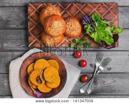 Vegetarian food vegetable cutlets for burgers parsley cherry tomatoes lettuce bread buns for burgers wooden dish gray background in rustic style top view