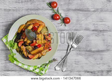 Steamed vegetables with rustic roasted potatoes eggplant zucchini peppers fresh cherry tomatoes rosemary cilantro basil thyme in green plate on light background white wooden top view