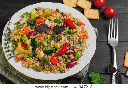 Vegan organic food salad with vegetables and cereals beans peas bread crackers cherry tomatoes seasoning for cereal salad greens cilantro basil thyme rosemary white porcelain plate dark black wood background