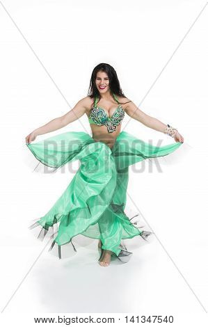 Young beautiful exotic eastern women performs belly dance in ethnic green dress. Isolated on white background. Studio shot