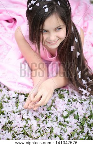 Beautiful little girl in pink dress with long brunette hair and smiling face lying on grass covered with spring flower blossom petals outdoor