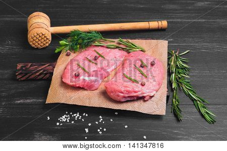Two meat pork steak chops wooden hammer for meat steaks chops rosemary dill parsley spices pepper salt paper black wooden background