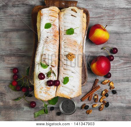 Assortment poppy seed strudel apple cinnamon strudel cherry strudel cheese raisin strudel fresh cherries apples poppy seeds raisins walnuts lemon balm tray white wooden background top view