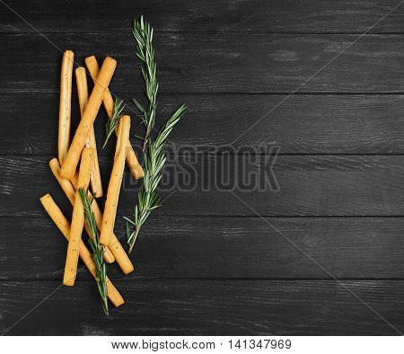 Bread sticks with thyme and fresh sprigs of rosemary on dark wooden background black empty space for text top view