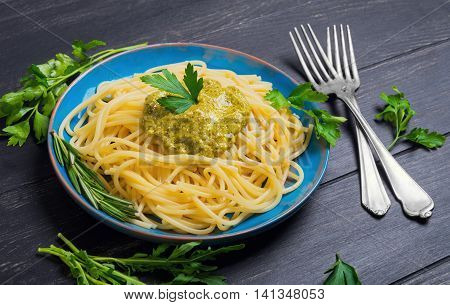 Pasta spaghetti with pesto sauce on blue ceramic plate greens for spaghetti rosemary parsley lettuce pesto sauce poured over spaghetti black wooden background