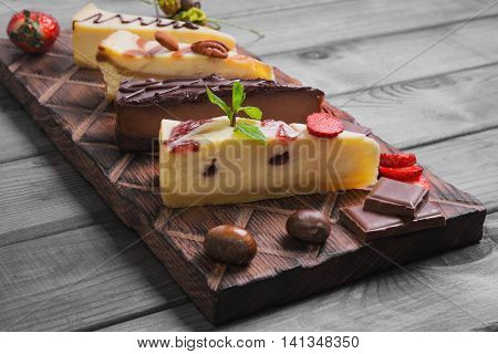 Assorted cakes cheesecake strawberry caramel chocolate caramel cut into pieces on wooden board fresh berries strawberry nuts chestnuts almonds pecans leaves mint gray wooden background