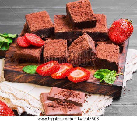 Pieces of chopped chocolate cake brownie with nuts chocolate bars leaves and sprigs of mint strawberry berries on cutting board black wooden background