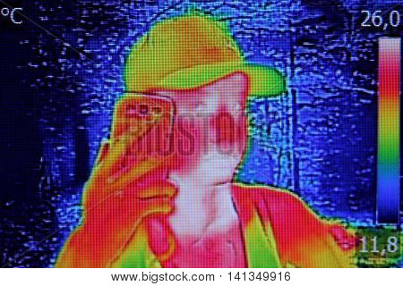 Infrared thermography image showing the heat emission when Young girl used smartphone or cell phone