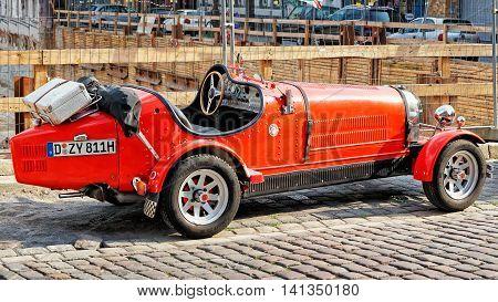 Dusseldorf Germany - May 3 2013: Old red car in the streets in the Old city center of Dusseldorf in Germany. It is the capital of Rhine Westphalia region.