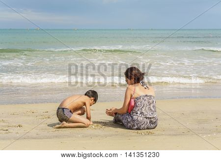 Mother And Son Sitting At The China Beach In Danang