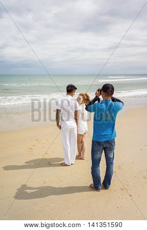 Young Couple And Their Photographer At The China Beach Danang