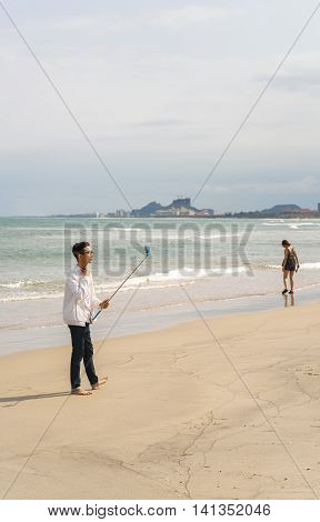 Young Fellow Using Selfie Stick On China Beach In Danang