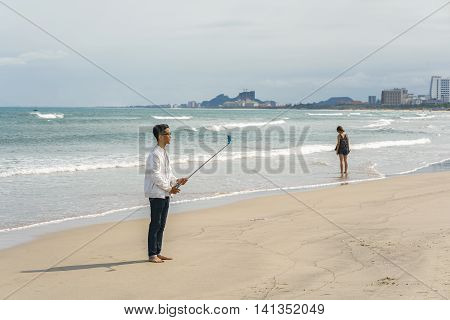 Young Fellow Using Selfie Stick At China Beach In Danang